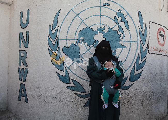 A Palestinian woman feeds her son during a protest a the decision made by the United Nations Relief and Works Agency (UNRWA) to reduce food aid delivered to the Gaza Strip in front of the UNRWA headquarters in Gaza City on April 9, 2014. Photo by Ashraf Amra