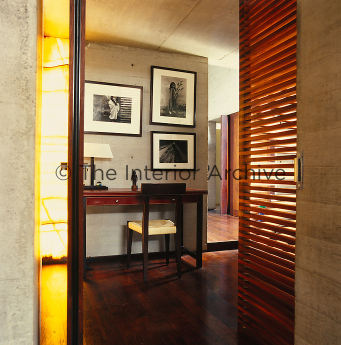 A collection of black and white photographs is displayed on the wall above a narrow wooden desk