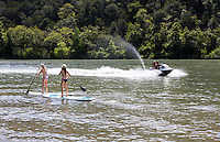 Two attractive females on stand up paddle board surfboard surfing together on Lake Travis as a jet ski races by on a hot summer's day in Austin, Texas.