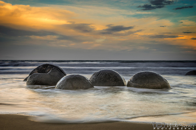 The Moeraki Boulders are unusually large and spherical boulders lying along a stretch of Koekohe Beach on the Otago coast of New Zealand between Moeraki and Hampden.