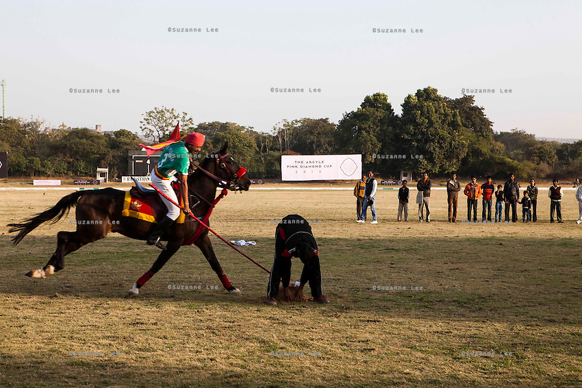 A 61st Cavalry rider rides at full speed past the spectators performing some trick riding called tent-pegging after a game between the Royal Jaipur Polo Team and the Western Australia Polo Team for the Argyle Pink Diamond Cup, organised as part of the 2013 Oz Fest in the Rajasthan Polo Club grounds in Jaipur, Rajasthan, India on 10th January 2013. Photo by Suzanne Lee