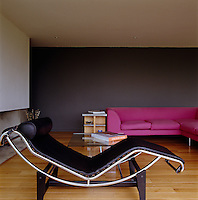 A black leather LC04 chaise by Le Corbusier stands in the corner of the living room by the fireplace