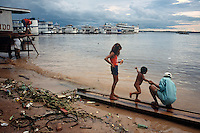 A boy gets a bath on the beach of the Rio Negro in Manaus, Brazil, Friday, Jan. 6, 2006. With few roads leading to the outside world, most goods are brought to the city 1,000 miles inland from the coast by boat. The river's beaches are a beehive of activity. (Kevin Moloney for the New York Times)