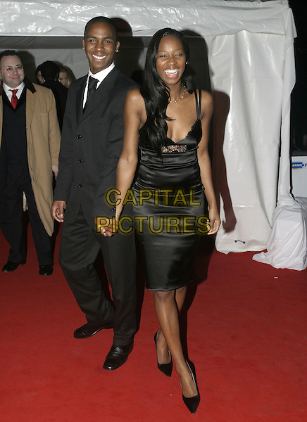 DARREN BYFIELD & JAMELIA .Moet & Chandon Fashion Tribute 2005, .Old Billingsgate Market, London, February 16th 2005..full length black satin dress holding hands.Ref: AH.www.capitalpictures.com.sales@capitalpictures.com.©Capital Pictures.