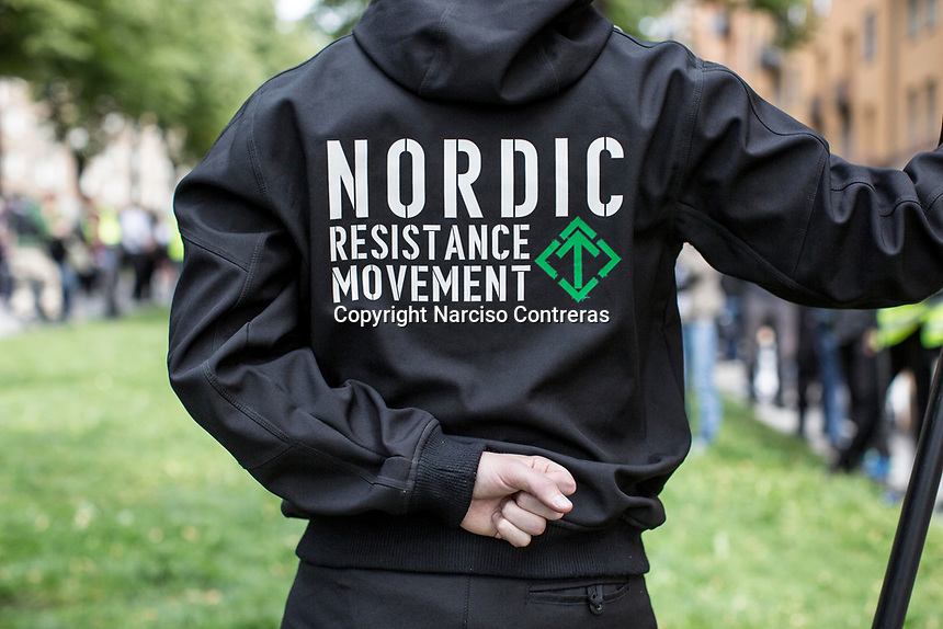 August 25, 2018: A supporter of the neo Nazi Nordic Resistance Movement NRM (Nordiska motståndsrörelsen) holds the movement's banner during a demonstration at the Kungsholmstorg square in Stockholm, Sweden. An estimate of 200 supporters of the neo-Nazi organisation held a six-hour rally guarded by a strong police deployment.