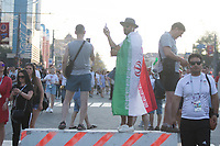 SARANSK, RUSSIA - June 25, 2018: An Iran fan takes photos while walking down Kommunisticheskaya Ulitsa to attend the 2018 FIFA World Cup group stage match between Iran and Portugal at Mordovia Arena.