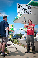 Chris Coyner of WFLA-TV interviews a protester holding a sign and waving at honking passerbys at a BP service station in St. Petersburg, Florida on Saturday, June 12, 2010. Volunteers from the Suncoast Seabird Sanctuary were on-hand to raise donations, Emergency Call List volunteers, and items & materials needed to prepare for injured birds and coastal cleanup,  Photo by Debi PIttman Wilkey