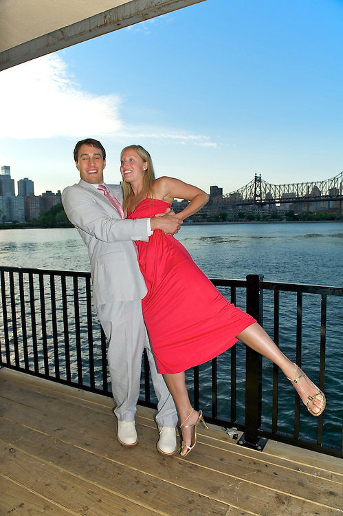 An engaged couple on the deck of The Water's Edge, LIC, with Manhattan skyline and Queensborough Bridge in background.