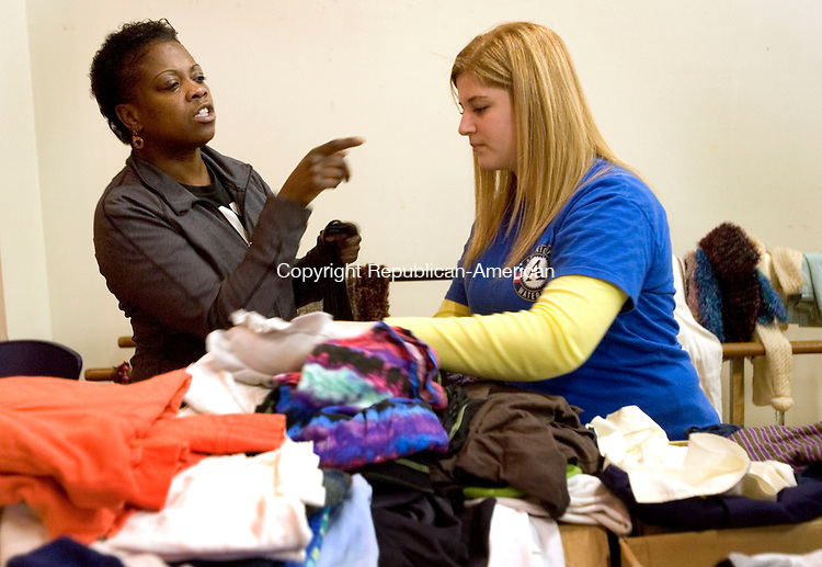 WATERBURY CT. 20 January 2014-012014SV01-From left, Charlene White of Waterbury gets some help shopping from Tina Fields of Waterbury during a cloths give away at New Opportunities Inc. in Waterbury Monday. The event was co-directed by NOW&rsquo;s Retired Senior Volunteer Program, Acts 4 Ministry, and with help from groups like Ameri-Corp., S.N.A.P., Stay-Well Health Center, D.S.S. among others. They expected to give out roughly 2,000 pounds of clothes, ranging from coats to children&rsquo;s wear that had been donated by&nbsp;New Opportunities and Acts 4 employee.<br /> Steven Valenti Republican-American