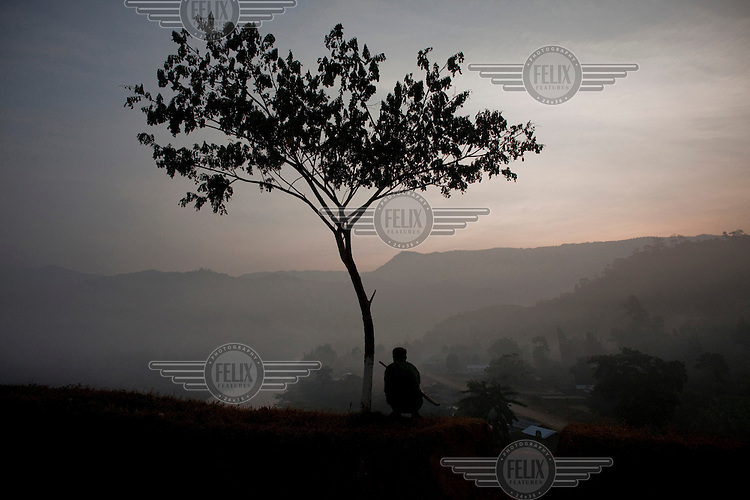 A Kachin Independence Army (KIA) soldier watches over a river which borders China, in Laiza, in KIA controlled territory in Kachin State. Despite the government reforms, there are still ongoing conflicts between the government Army and armed ethnic groups such as the Kachin.