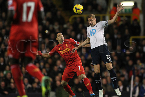 15.12.2013. White Hart Lane, London, England. Michael DAWSON of Tottenham Hotspur wins the header against Luis SUÁREZ of Liverpool compete for the ball during the Barclays Premier League match between Tottenham Hotspur and Liverpool at White Hart Lane.