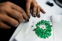 An emerald cutter sorts out rough emeralds seen before being processed in a cutting and polishing workshop in Bogota, Colombia, 7 February 2014. Approximately 60 percent of the world's total amount of emeralds come from Colombia. Most of the rough gems are processed in workshops located in the emerald district in downtown Bogota. Due to their special clarity and deep vivid green color, Colombian gemstones are considered the most beautiful emeralds in the world.