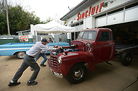 NWA Democrat-Gazette/ANDY SHUPE<br /> Clem Johnson (left), owner of Tuba Trucks, and mechanic Phillip Daniel push a 1952 Chevrolet flatbed truck into a garage bay Wednesday, Oct. 11, 2017, while working at the longtime restoration and customization shop at 1798 E. Huntsville Road in Fayetteville. The shop will host the Old Truck Cruise-In and Toy Drive at 1 p.m. Saturday with live music and food. Admission is a new toy to benefit the U.S Marine Corps Reserve Toys for Tots Program.