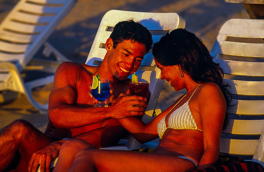 Couple enjoying cocktails on the beach, Reef Club Beach Resort, Isla Cozumel, Mexico