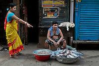 A Bangladeshi woman buys fish from a fish vendor on a road early morning in Dhaka, Bangladesh.