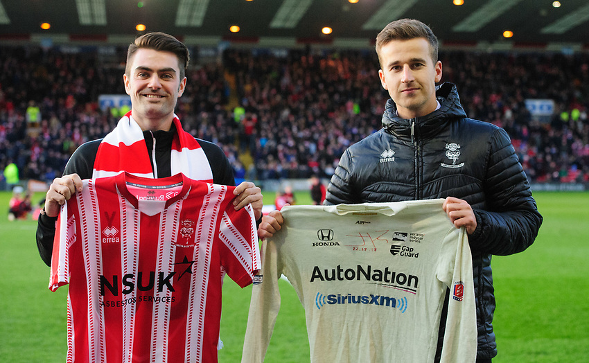 Racing driver Jack Harvey and Lincoln City marketing manager Jake Longworth, representing the club, exchange shirts prior to the game<br /> <br /> Photographer Chris Vaughan/CameraSport<br /> <br /> The EFL Sky Bet League Two - Lincoln City v Newport County - Saturday 22nd December 201 - Sincil Bank - Lincoln<br /> <br /> World Copyright © 2018 CameraSport. All rights reserved. 43 Linden Ave. Countesthorpe. Leicester. England. LE8 5PG - Tel: +44 (0) 116 277 4147 - admin@camerasport.com - www.camerasport.com