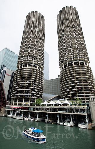 26 JUN 2014 - CHICAGO, USA - A boat passes Marina City, two corn cob shaped towers which overlook the Chicago River in Chicago in the USA (PHOTO COPYRIGHT © 2014 NIGEL FARROW, ALL RIGHTS RESERVED)