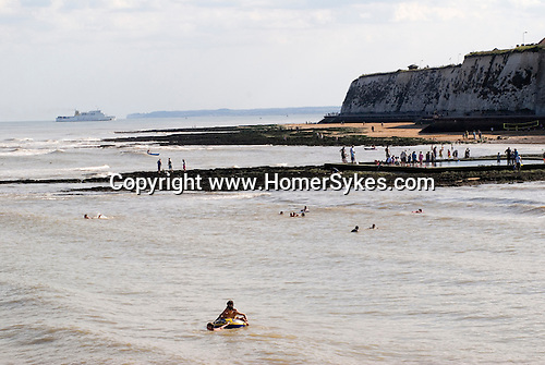 Broadstairs Kent UK. Summer holiday tourism looking west along the coast towards Ramsgate. Ramsgate Ostend ferry coming in to port.