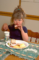 Girl eating lunch of peanut butter and jelly sandwiches age 3.  Western Springs  Illinois USA
