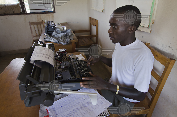 A medical worker types up notes in a health centre.
