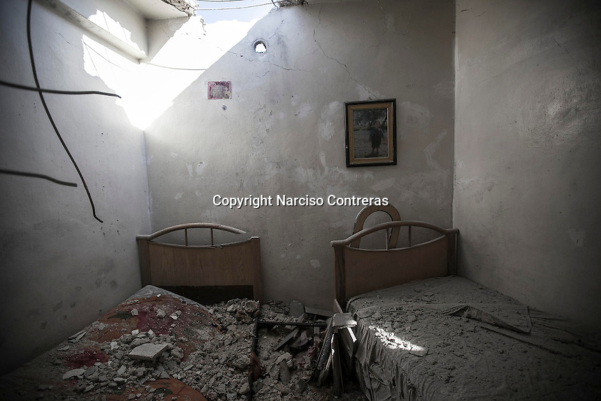 A hole in the ceiling is showed up from a kids bedroom in one apartment at the upper level of a building hit by mortar shelling in Bustan Al-bashar district at the northeast of Aleppo City.