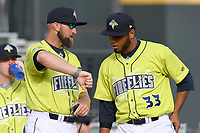 Pitching coach Roybe Ring checks the time with starting pitcher Jaison Vilera (33) of the Columbia Fireflies before a game against the Charleston RiverDogs on Saturday, April 6, 2019, at Segra Park in Columbia, South Carolina. Columbia won, 3-2. (Tom Priddy/Four Seam Images)