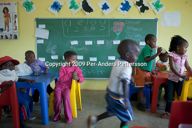 MADIKWE, SOUTH AFRICA - SEPTEMBER 11: Children play at a pre-school financed by Thakadu River Camp on September 11, 2009, in Madikwe, South Africa. The lodge is community owned by a village nearby called Molatedi. All the employees at the lodge come from the village. The reserve was claimed in 1991 and over eight thousand animals were moved to the reserve during a period of six years. Its bordering Botswana, and its about 3 hours drive from Johannesburg. The size of the reserve is about 75 000 hectares. (Photo by Per-Anders Pettersson/Getty Images) .