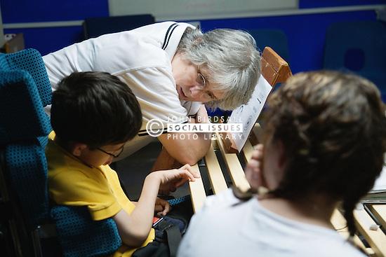 Disabled children talking to their teacher,