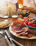 Antipasto plate with cured meat, pickled onions and red peppers, with silverware beside it. In the background are a bowl of olives, large wedges of cheese, drink glasses, and bread baguette.