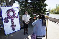 "Black woman posing by Prince life-size purple floral ""Love Symbol"". Paisley Park Studios Chanhassen Minnesota MN USA"