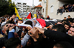 Mourners carry the body of Palestinian Hamza Zamareh during his funeral in Halhoul, in the West Bank city of Hebron on February 17, 2018. Hamza stabbed a security guard at the entrance of the Israeli settlement Karmei Tzur north of Hebron and was shot dead, the Israeli army said, in the latest violence in the occupied West Bank. Photo by Wisam Hashlamoun