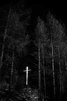 Switzerland. Canton Graubunden. Samnaun. An illuminated christian cross at night in the forest. Samnaun (Romansh: Samignun) is a high Alpine village and a valley at the eastern end of Switzerland and a municipality in the Engiadina Bassa / Val Müstair Region. 24.11.2017 © 2017 Didier Ruef