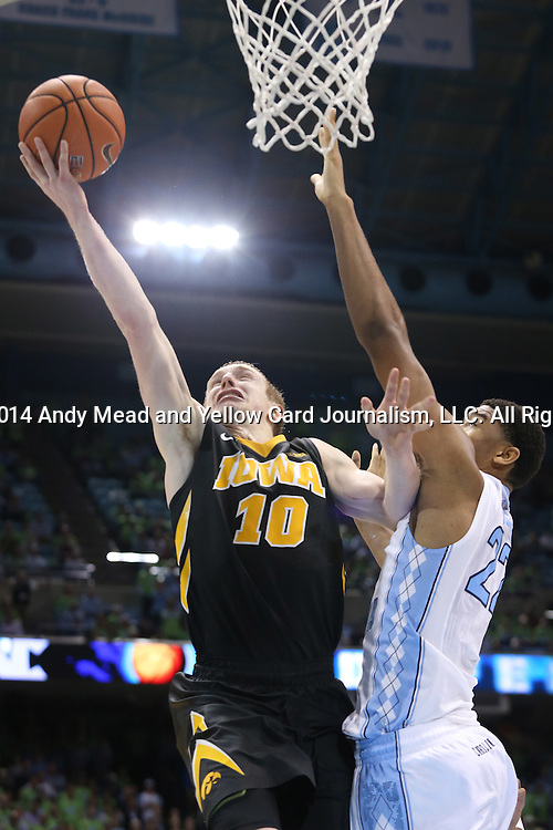 03 December 2014: Iowa's Mike Gesell (10) scores the game-winning basket while being fouled by North Carolina's Isaiah Hicks (22). The University of North Carolina Tar Heels played the University of Iowa Hawkeyes in an NCAA Division I Men's basketball game at the Dean E. Smith Center in Chapel Hill, North Carolina. Iowa won the game 60-55.