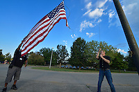Security Monitor Anthony Wheat, left, and Plant Operator Vince Ayers raise the American Flag at Okolona Elementary on the first day.