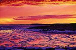 Sunset colors are reflected in the water of Wager Bay, littered by ice from the spring breakup.<br /> Northwest Territories, Canada