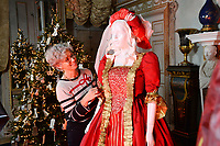 """BNPS.co.uk (01202 558833)<br /> Pic: ZacharyCulpin/BNPS<br /> <br /> Denise applies the finishing touches to a lady in red.<br /> <br /> Ori-garments -  Artist Denise Watson has created a stunning 1750's masquerade Christmas Ball with characters made entirely from paper at the National Trust's Uppark House in West Sussex.<br /> <br /> Denise has dressed 14 shop mannequins with clothes, shoes, masks, fans, floral details, hair and even jewellery made from things like tissue paper, gift wrap and brown parcel paper. <br /> <br /> The festive display was inspired by Admiral Lord Gambier's memoirs in which he quotes from Lady Sarah Featherstonhaugh's journal of 1753 where she wrote: """" The whole party afterwards proceed to Uppark, where they passed a cheerful happy Christmas in the most friendly society, and enlivened their neighbourhood with some masked balls.""""<br />  <br /> The design to the finished result took a total of three months. Denise said, """"I am really delighted with the final result. It has been a joy to work at Uppark using the grand rooms and to recreate an event which actually took place""""."""