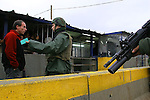 An Israeli soldier prevents from a Palestinian man to cross the Hawara checkpoint in Nablus, West Bank, November 05, 2006. The Hawara checkpoint on the southern entrance of Nablus controls the movement of Palestinians between Nablus and the Southern part of the West Bank. The checkpoint, run by IDF paratroopers, doesn't limit with Israel. Photo by Quique Kierszenbaum