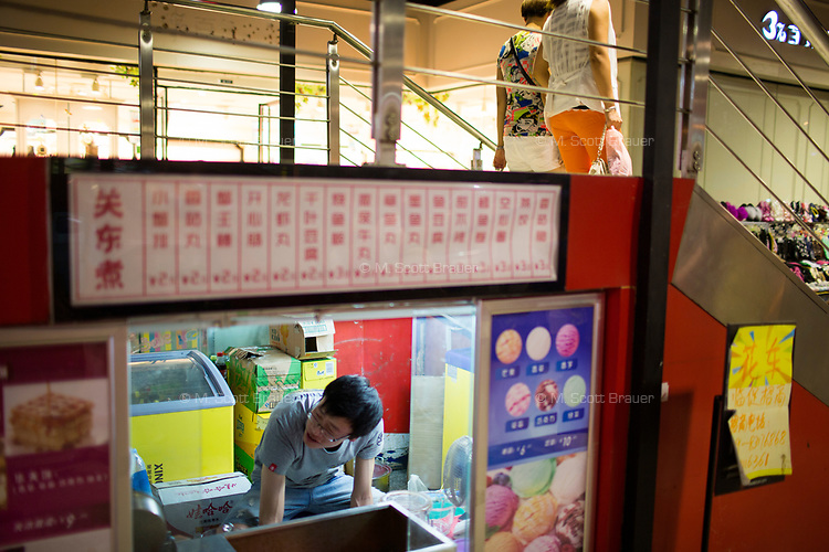 A man waits for customers in a dessert and ice cream kiosk under a shopping mall staircase in Xian, Shaanxi, China.