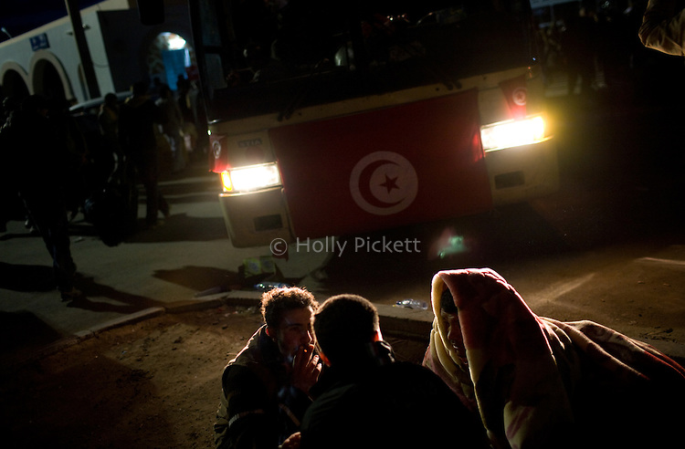 Men are illuminated by the headlights of a bus departing for the Tunis airport, at the border crossing with Libya near Ben Guerdane, Tunisia, Thursday, Feb. 24, 2011. Foreign nationals, including many Egyptian workers, fled Libya as Col. Muammar Qaddafi tried to maintain his grip on the capital Tripoli. In the latest uprising to strike the Middle East, street protests which began in Eastern Libya spread to Tripoli, as opposition members called for Qaddafi to follow Tunisian president Zine el-Abidine Ben Ali and Egyptian president Hosni Mubarak and step down.