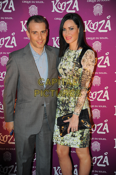 Will Stoppard & Linzi Stoppard.Opening night of  the Cirque du Soleil's 'Kooza' at the Royal Albert Hall - Arrivals.London, England..January 8th, 2013.half length black green print dress grey gray suit blue shirt black clutch bag married husband wife .CAP/CAS.©Bob Cass/Capital Pictures.