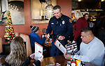 Casey Drews, with Carson City Fire, talks with guests as first responders from around the area wait on diners at Bodines as part of the Feast with a Hero fundraiser in Carson City, Nev., on Saturday, Dec. 15, 2018. <br /> Photo by Cathleen Allison/Nevada Momentum