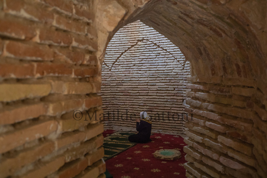 Uzbekistan - Tashkent - A muslim woman prays inside the Zayniddin Bobo Mausoleum, built in the 16th century.