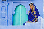 Rajasthani girl in traditional clothes sitting in front of house in Blue City (old town); the blue houses were originally for Brahmins but non-Brahmins soon joined in, as the colour was said to deflect the heat and keep mosquitoes away, Jodphur, Rajasthan, India --- Model Released