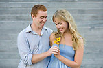 A young redhead man gives his pretty blond girlfriend flowers.