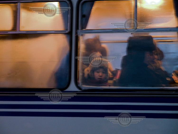 Boy sitting behind a window of a Yakutsk bus.