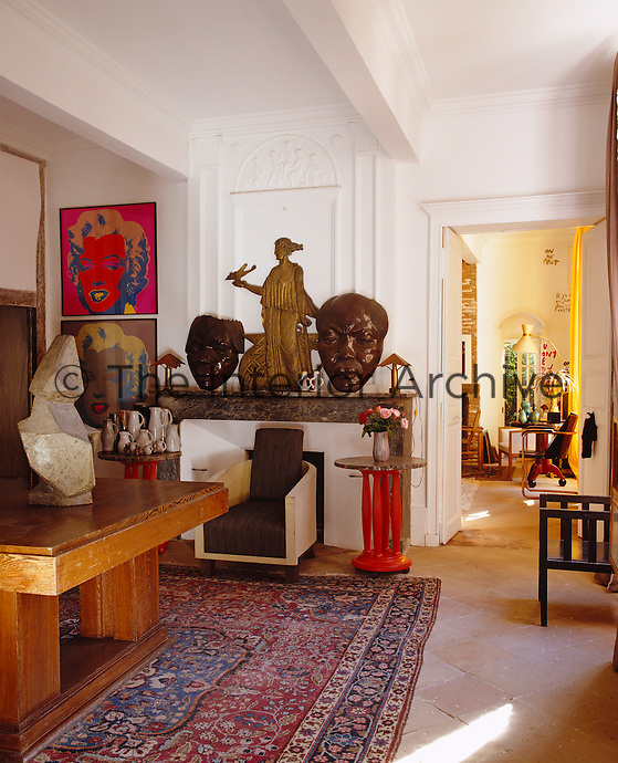 A collection of sculptures artworks and jugs are on display in the ante-room along with a Modernist armchair