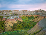 Badlands National Park, SD  <br /> Bands of pastel colored hills and cliffs with Yellow Sweet Clover (Melilotus officinalis) in the spring washes