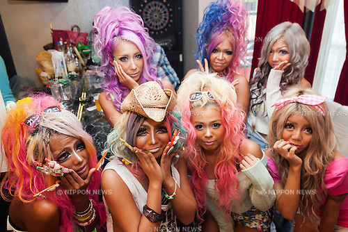 Members of staff pose for pictures at the Ganguro Cafe &amp; Bar in the Shibuya shopping area on September 4, 2015. <br /> <br /> Ganguro is an alternative Japanese fashion trend which started in the mid-1990s where young women, rebelling against the traditional idea of Japanese beauty, wore colorful make-up and clothes and had dark-skin.<br /> <br /> 10 Ganguro fashion girls work in the new bar, which offers original Ganguro Balls (fried takoyaki style sausage balls in black squid ink batter) on its menu. Ganguro Caf&eacute; &amp; Bar also offers special services such as Ganguro make-up and the chance to take purikura (photo booth pictures) with staff and to look like a Ganguro girl walking around the Shibuya streets.<br /> <br /> The bar is popular with both Japanese and foreigners and has menus translated in English. (Photo by Rodrigo Reyes Marin/AFLO)