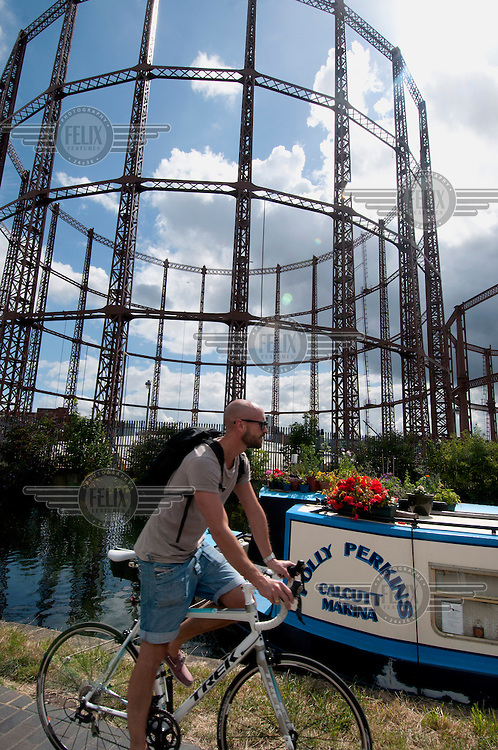 A man on a bicycle passes a canal boat and gasometers along Regents Canal in London.