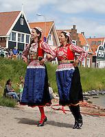 Volendammerdag in Volendam. Mensen dansen op het strandje in klederdracht uit Marken